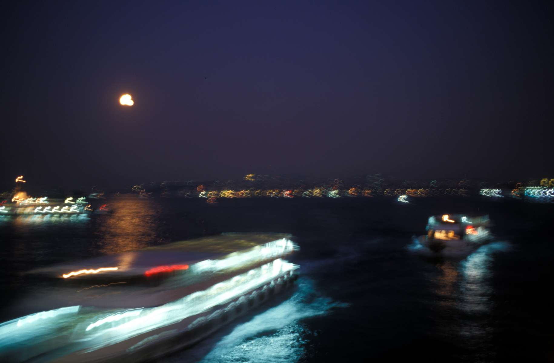 As the moon rises over the Bosphorus Straits, two ferries pass in the night. Every day thousands of people use the ferries to commute between the European and Oriental sides of the city, crossing the Golden Horn, the Marmara Sea and the Bosphorus Straits. November 2004.