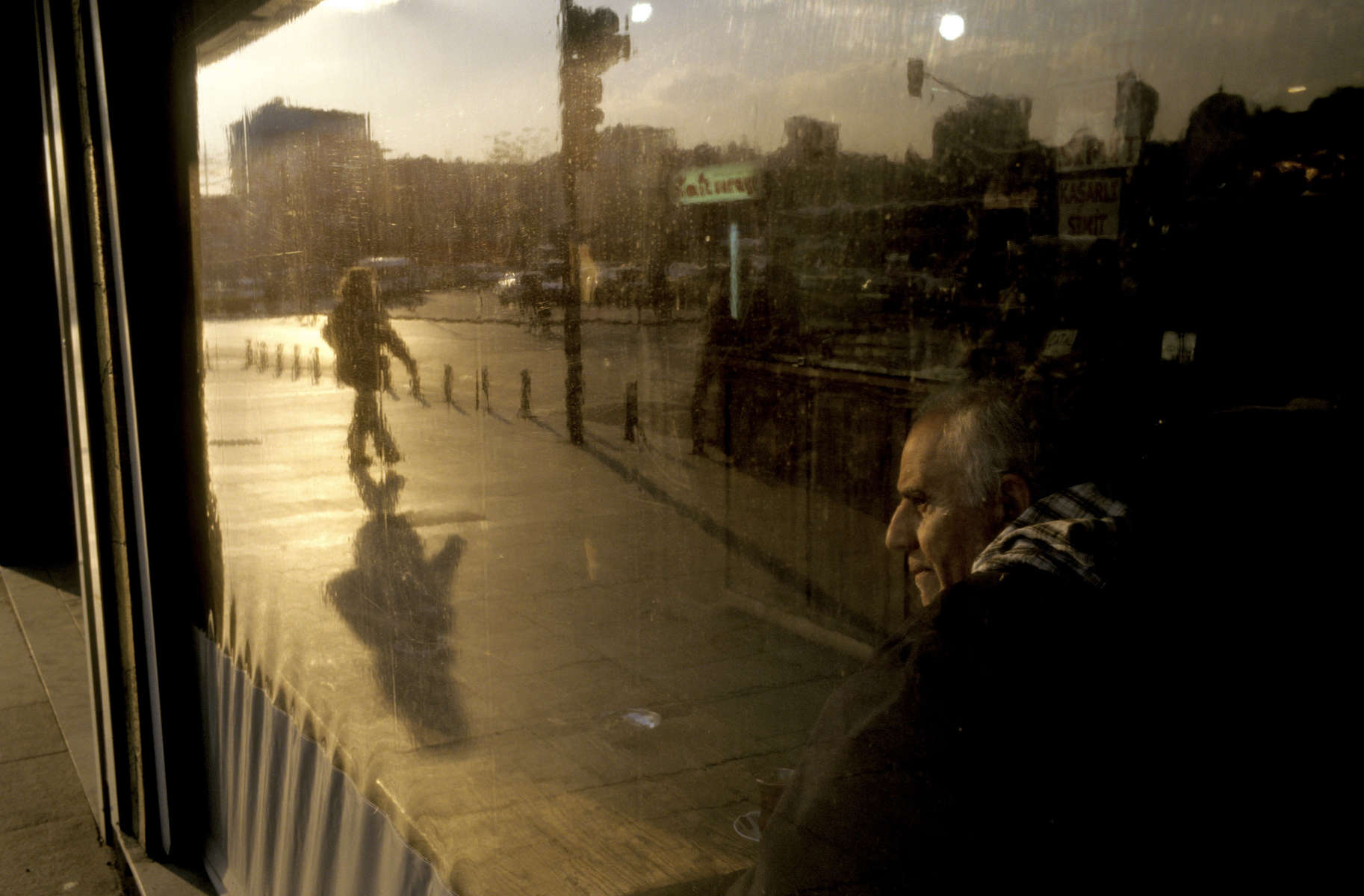 As the sun sets over Istanbul\'s Istiklal Square, a coffeehouse window captures the reflection of a pedestrian passing on the street while inside, a customer drinks coffee and watch the world outside.