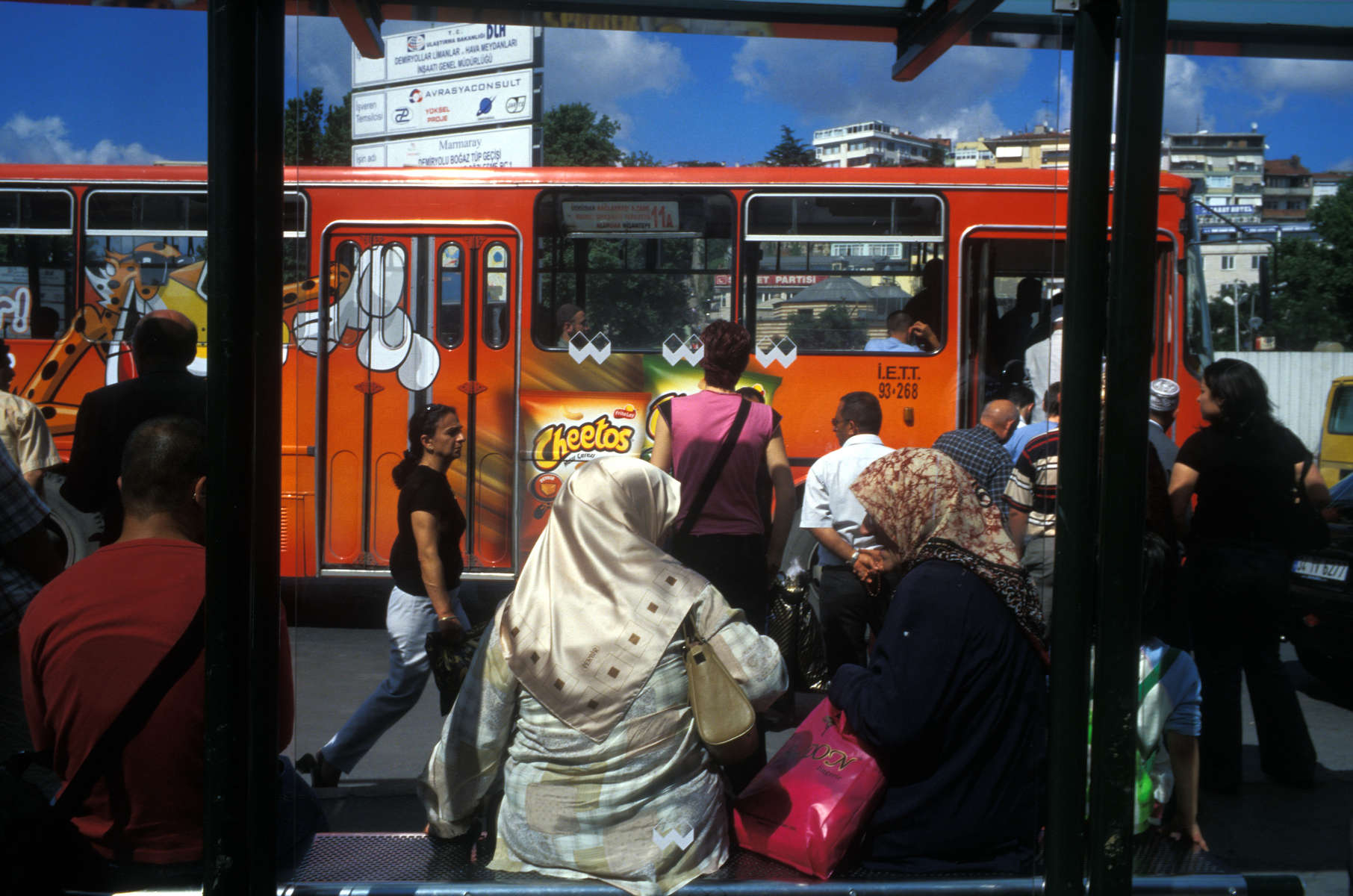 Religiously observant Muslim women in head scarves and pedestrians in Western dress waiting a bus stop illustrate the many ways the secular and sectarian intersect in Istanbul. June, 2005.