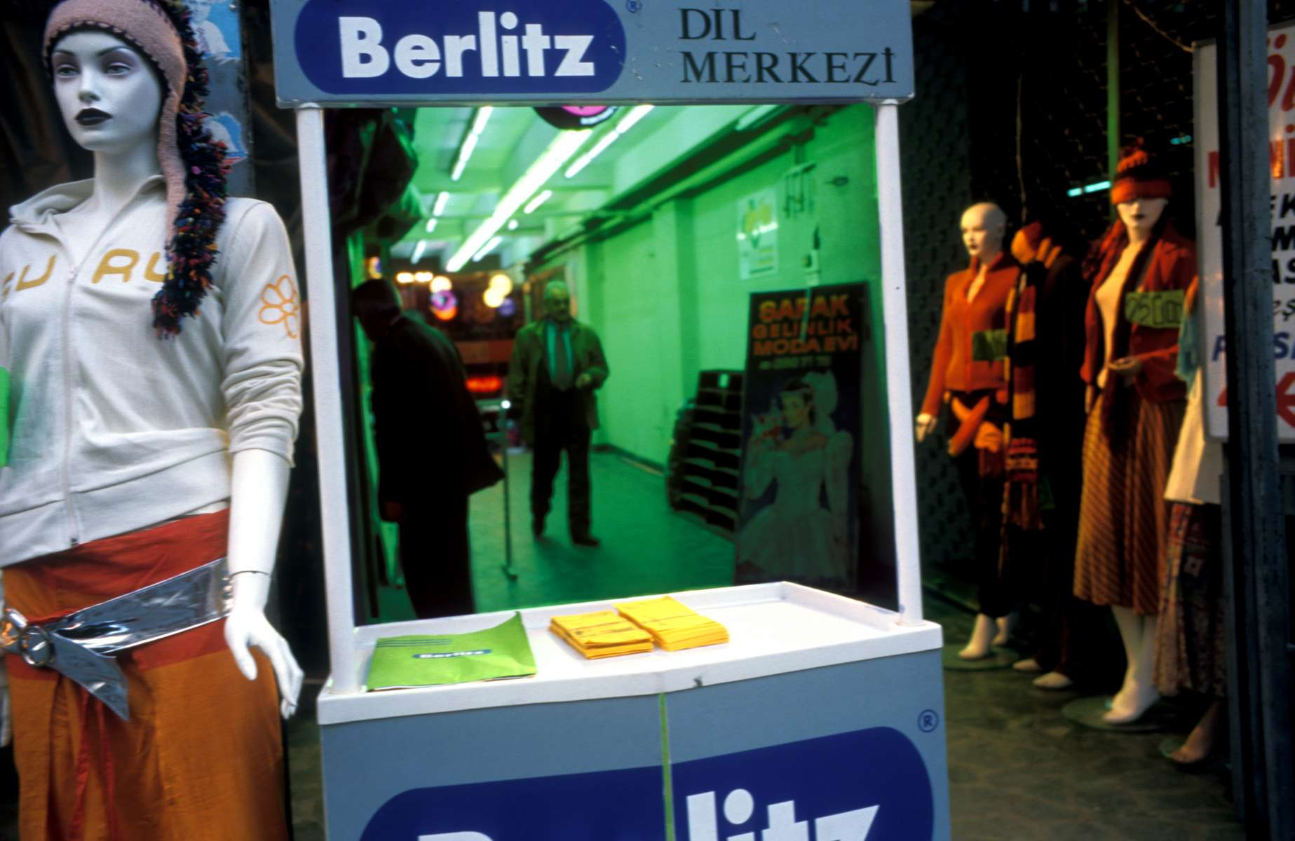 On Istiklal Caddesi, Istanbul\'s busy pedestrian street, mannequins line a shopping arcade, with an information booth for a Berlitz language program in front. Istiklal is filled with western-style clothing stores and international name-brand boutiques -- a reflection of the western values and culture held by many Turks. November 2004.