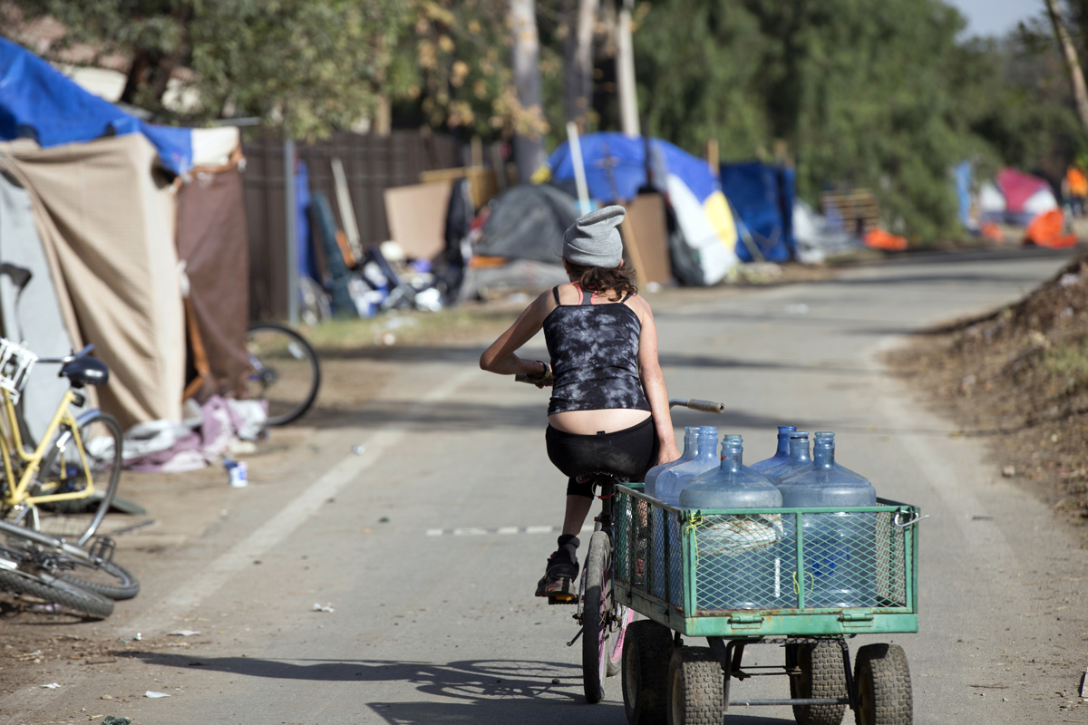 In mid-January, Crystal, a well-liked resident of the encampment, hauls water bottles to the public drinking fountain where she will fill the bottles and deliver them to other residents, for a small fee.