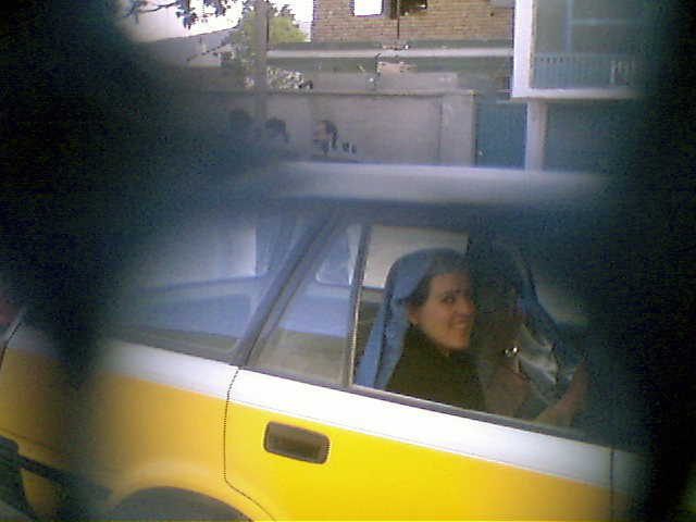 Women with their burkas thrown back over their heads in the back seat of a taxi.