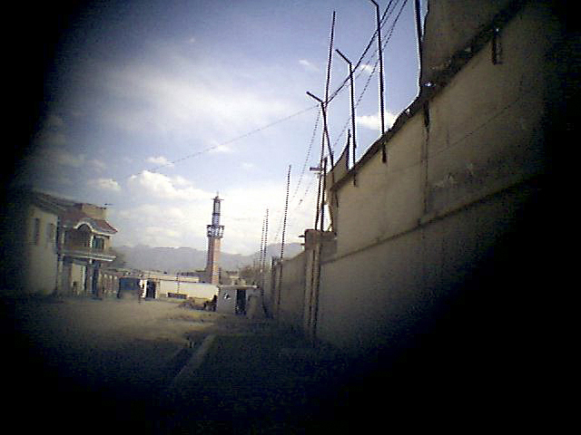 The minaret of a mosque stands at the end of a street.