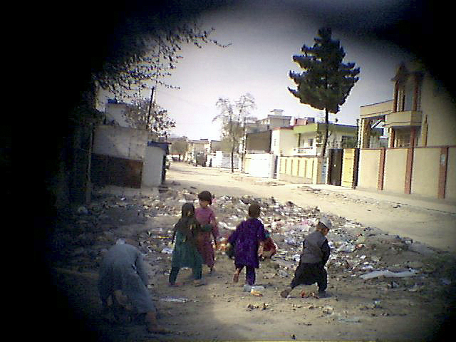 Children play in a trash heap dumped in front of their home in a Kabul neighborhood. There are no sanitation services in the city.