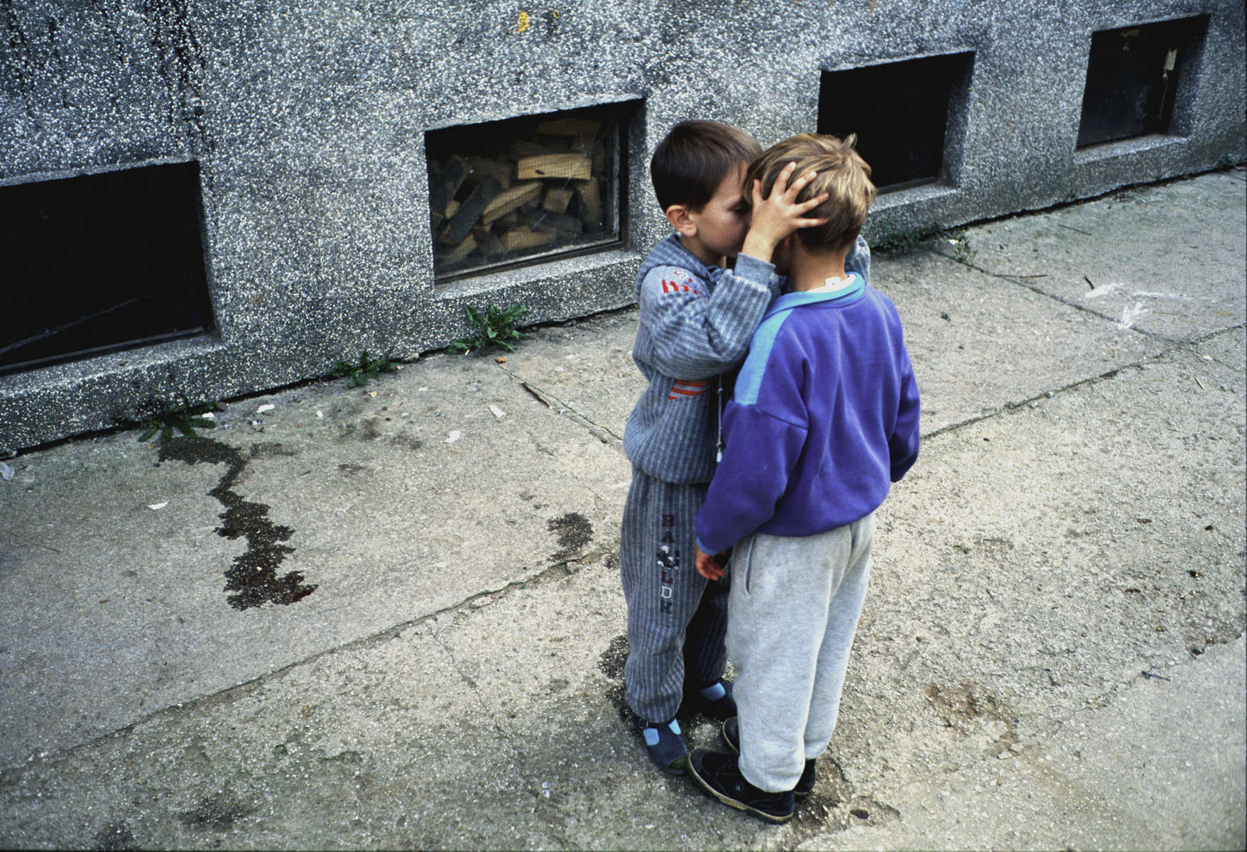 Two boys on a sidewalk in a suburb of Sarajevo are among the thousands of refugees who fled to the city at the end of the war, after the massacre of some 7,000 to 8,000 Muslim men and boys at the hands of Bosnian Serb forces. The fathers of both boys were killed in the massacre. October 2000.