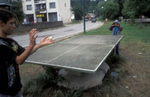Two boys play a makeshift game of ping pong, with no net and no paddles.