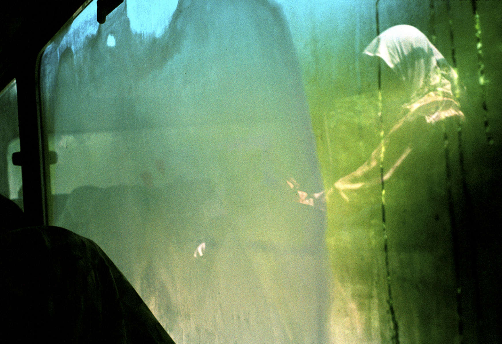 On the day groundbreaking ceremonies are held for a memorial to the 7,000 to 8,000 Muslim men and boys killed by Serbs in the 1995 Srebrenica massacre, a widow is seen reflected in bus window, where condensation has marked the surface of the glass.