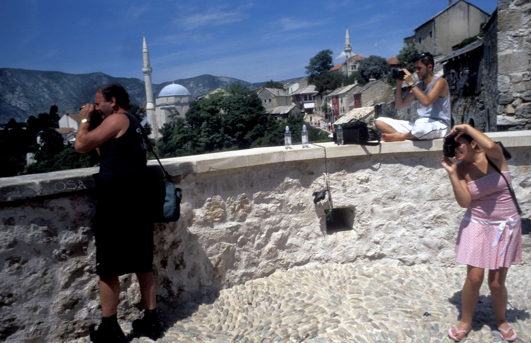 Tourists taking pictures of the rebuilt Mostar Bridge, the day after dedication ceremonies marking the completion of the work.
