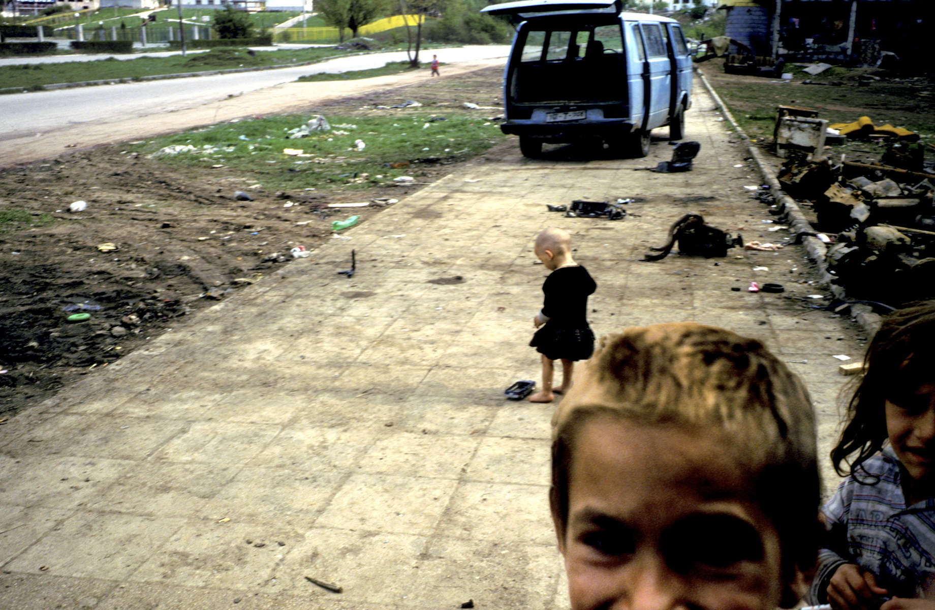 Roma children, squatting with their families in one of the many buildings riddled by mortars during the siege of Sarajevo, play on a junk-littered sidewalk.