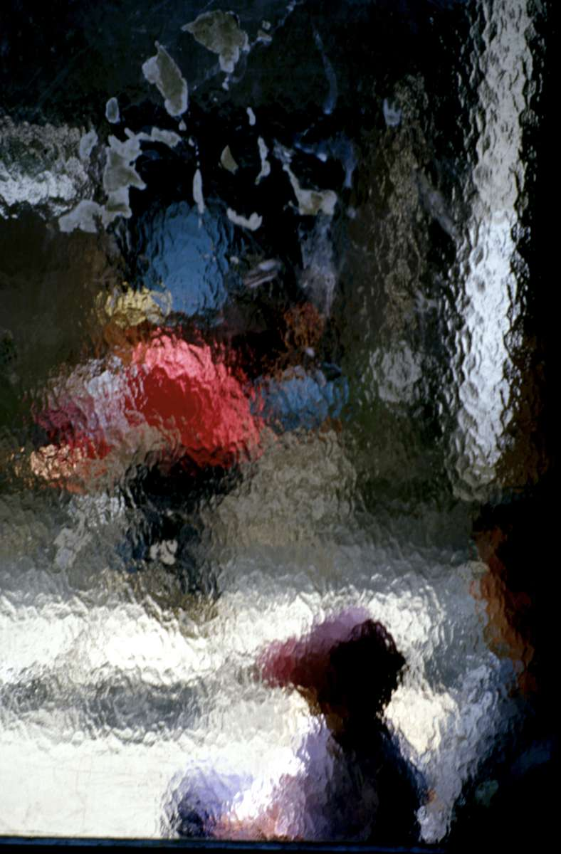 Srebrenica refugees, still without permanent housing eight years after the end of the war, seen through a textured glass window.