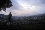 From one of the hillsides that climb up from Sarajevo, a man looks out over the city at sunset. July 2004.