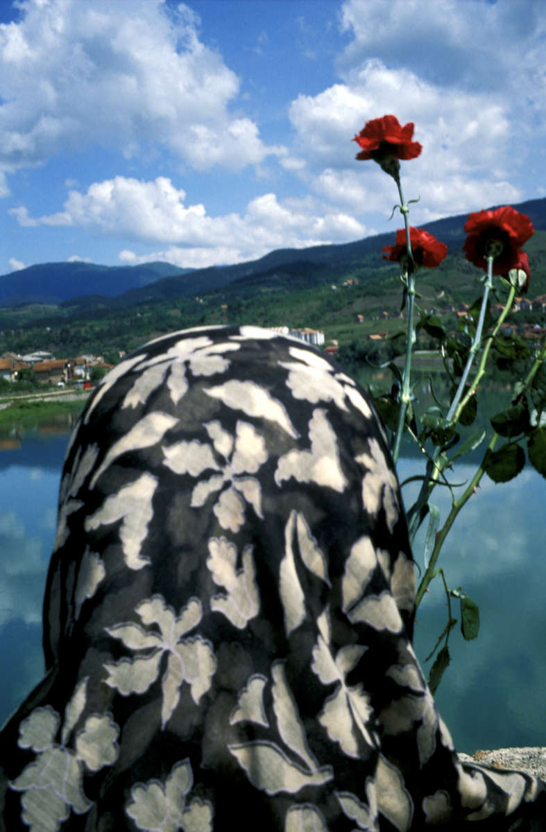 A Muslim widow gets ready to throw red carnations in to the Drina River, marking the spot where some 2,000 Muslim men and boys were executed during the \{quote}ethnic cleansing\{quote} campaign waged by Serbs against their neighbors in the early months of the 1992-95 war. The bridge, built during the Ottoman Empire, was made famous by the Nobel Prize-winning author Ivo Andric in his book, \{quote}Bridge on the River Drina.\{quote}