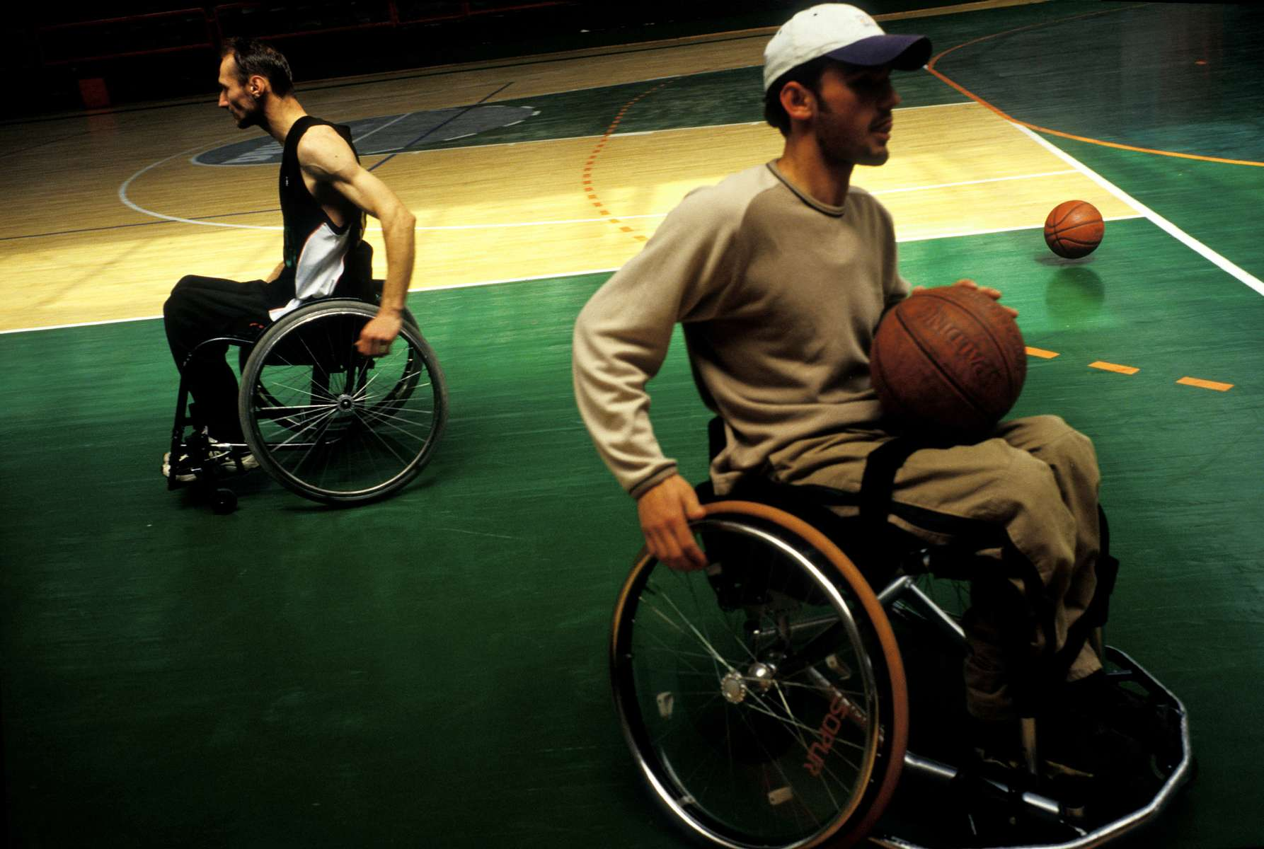Members of the 3K Sarajevo wheelchair basketball team during a break from practice. Most of the players were wounded as civilians or as soldiers on the frontline during the 1992-95 war. The young man in the foreground was shot by a sniper when his parents let him go outside to celebrate his thirteenth birthday. Bosnia now has eight wheelchair basketball teams, made up almost entirely of young men wounded during the war.