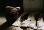 Muslim widow examines body bags containing the remains of recently exhumed victims of the 1992 \{quote}ethnic cleansing\{quote} campaign waged by Serbs against their Muslim neighbors. Exhumations of mass graves began in 1996 and are expected to last for many years to come. Nearly 30,000 Muslims -- most of them civilians -- were listed as missing at the end of the war; most are believed to have been victims of \{quote}ethnic cleansing.\{quote} July 2001