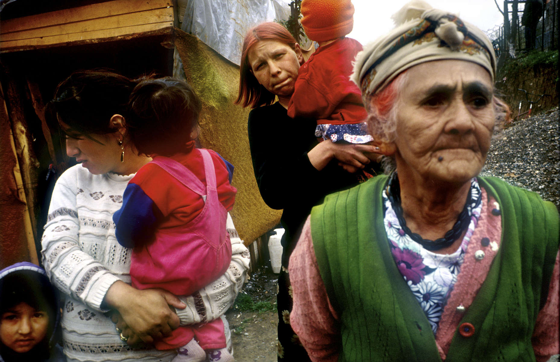 A Roma woman with her daughters-in-law and grandchildren stands in front of a makeshift home in the village of Strazenica. During the war, gypsies were also \{quote}cleansed\{quote} by Serbs; these gypsies were forced to leave their homes and have returned to rebuild.