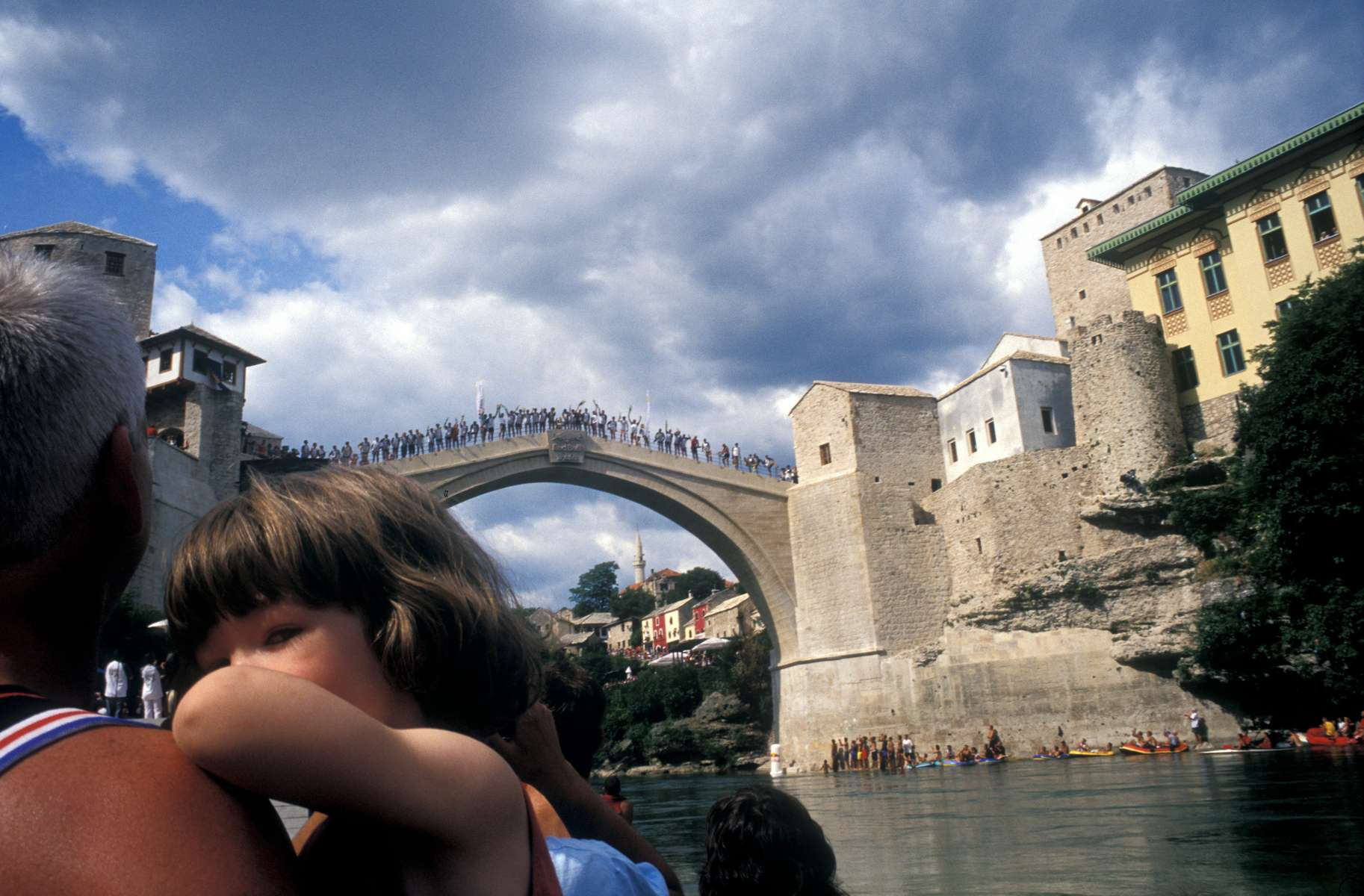While crowds line the banks of the Neretva river, competitors line the top of the famed Mostar Bridge, ready to begin what locals say is the city\'s 448th annual jumping and diving contest. The competition was held just eight days after the newly rebuilt bridge was opened.