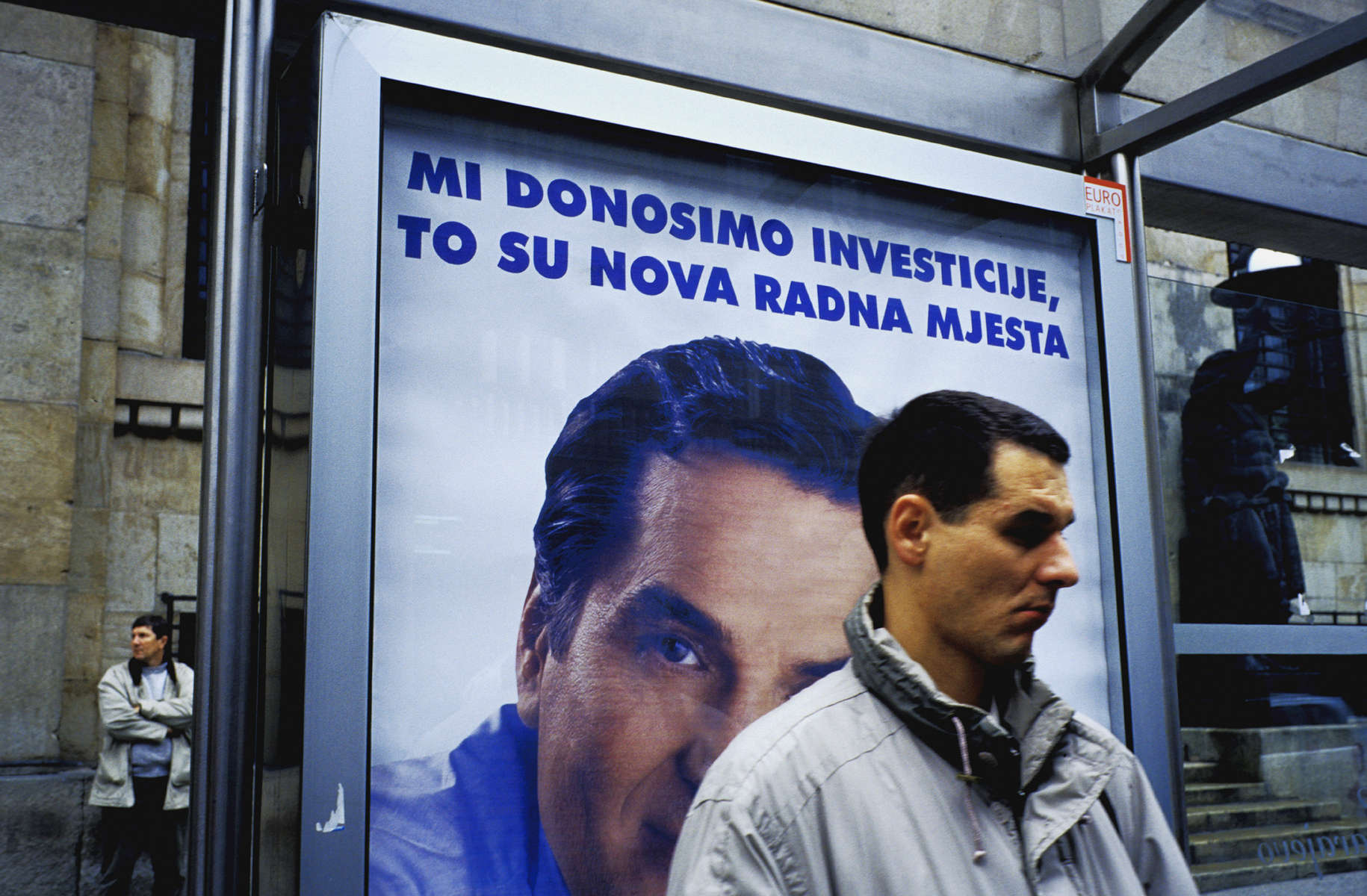 At a bus stop in Sarajevo, an election poster for the moderate \{quote}Stranka za BiH\{quote} party (Party for Bosnia Hercegovina) reads, in rough translation, \{quote}Through investment, to new jobs.\{quote} The slogan is a reference to the country\'s troubled economy, and its unemployment rate of nearly fifty percent. The man in the poster is Haris Silajdzic, who served as prime minister during the war. In this election, all the moderate parties were defeated, as voters returned nationalist parties to power. September 2002.