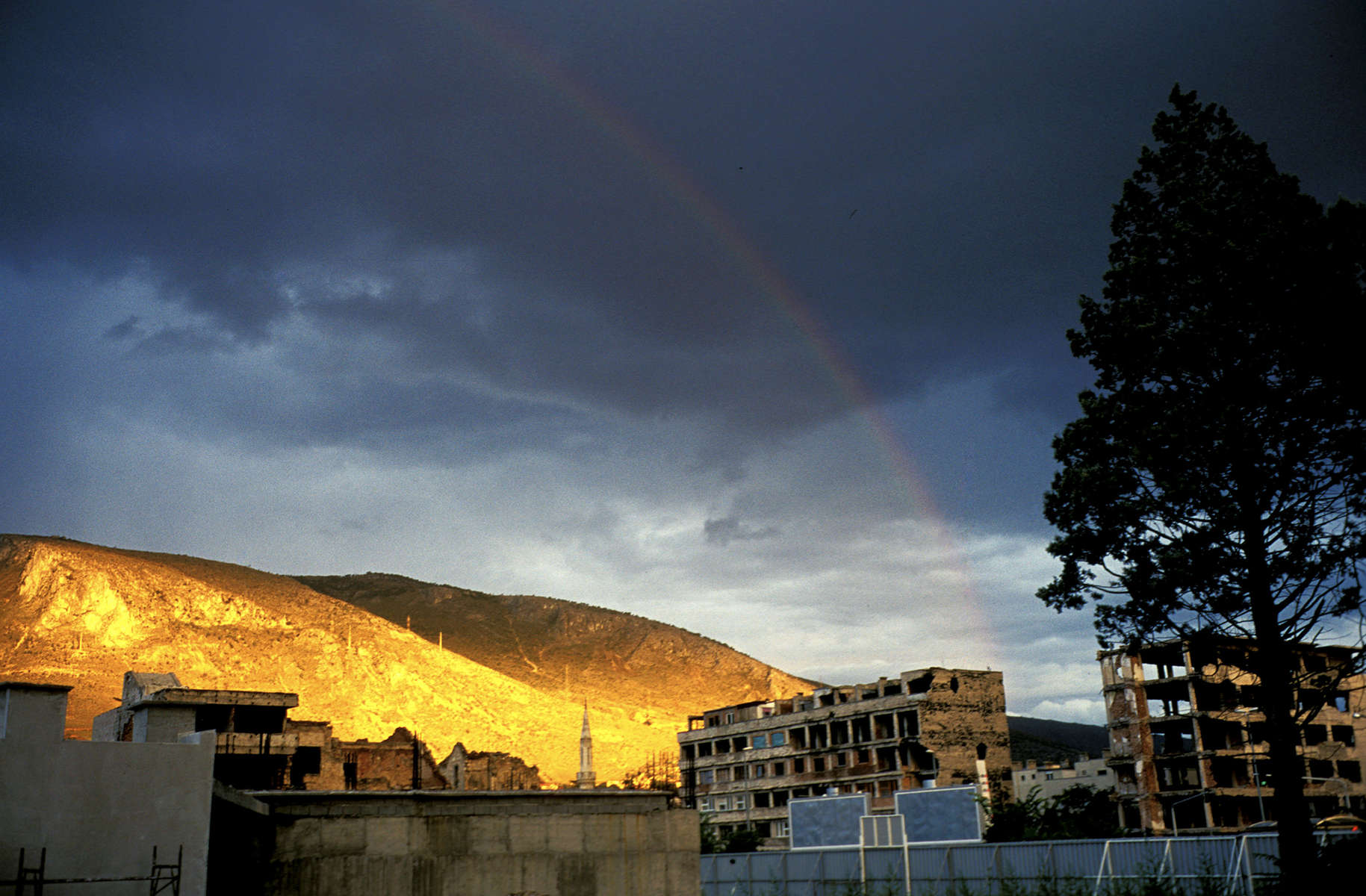 At the end of a stormy day, the setting sun causes a rainbow to arch over the hills around the town of Mostar, the scene of some of the most vicious fighting during the war. At lower right, stand destroyed buildings that still line the street which marked the frontline between Muslim and Croat forces.