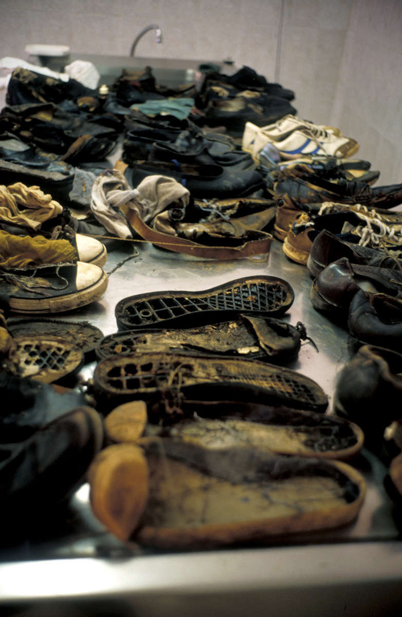Shoes retrieved from a mass grave lie on a table in a morgue. Julyl 2001.
