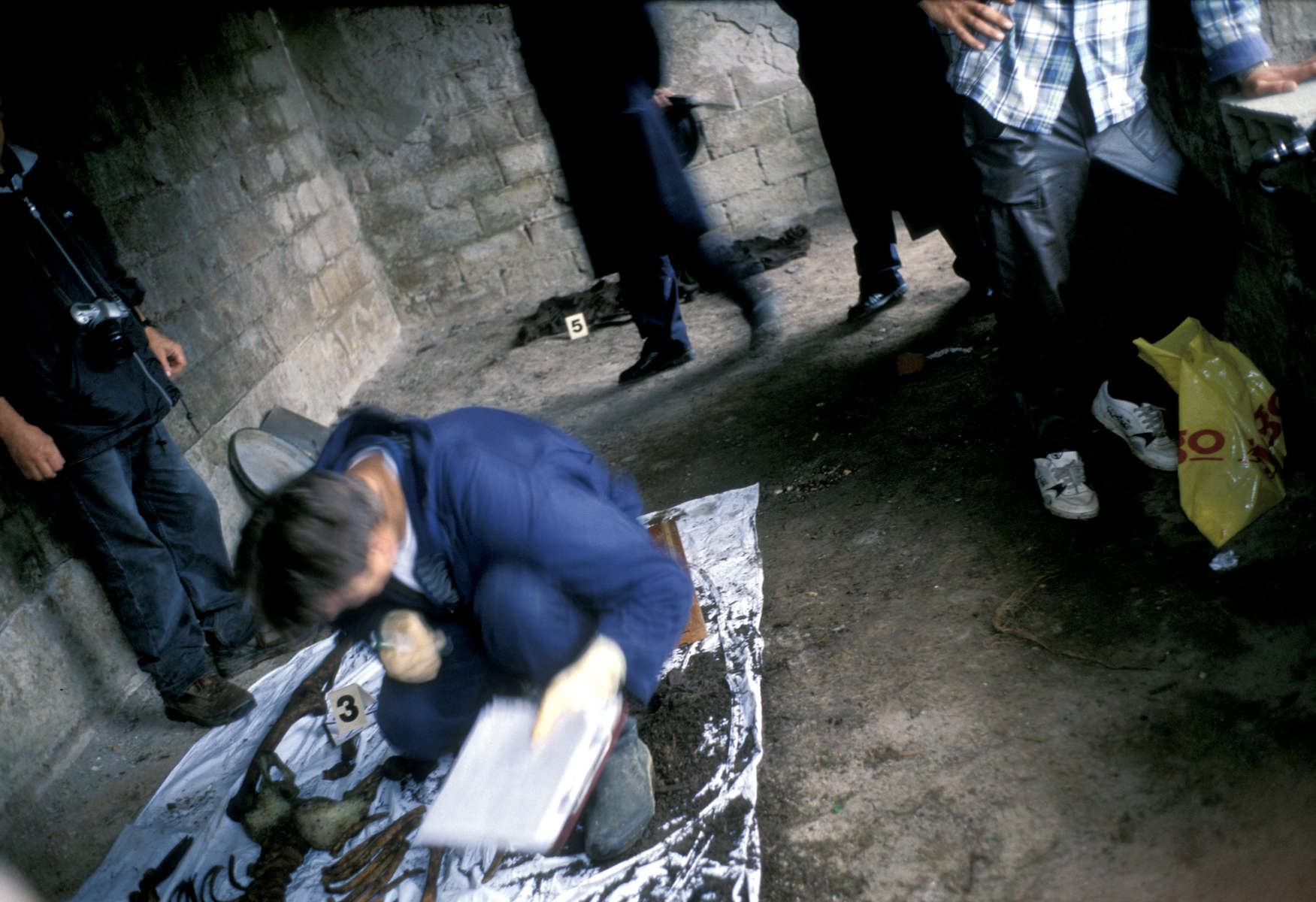 Police crime scene technicians examine the remains of a Muslim man killed in May 1992 and exhumed eight years later. Every exhumation is attended by crime scene experts who send their reports to the war crimes tribunal at The Hague for use in possible prosecution there. October 2000.