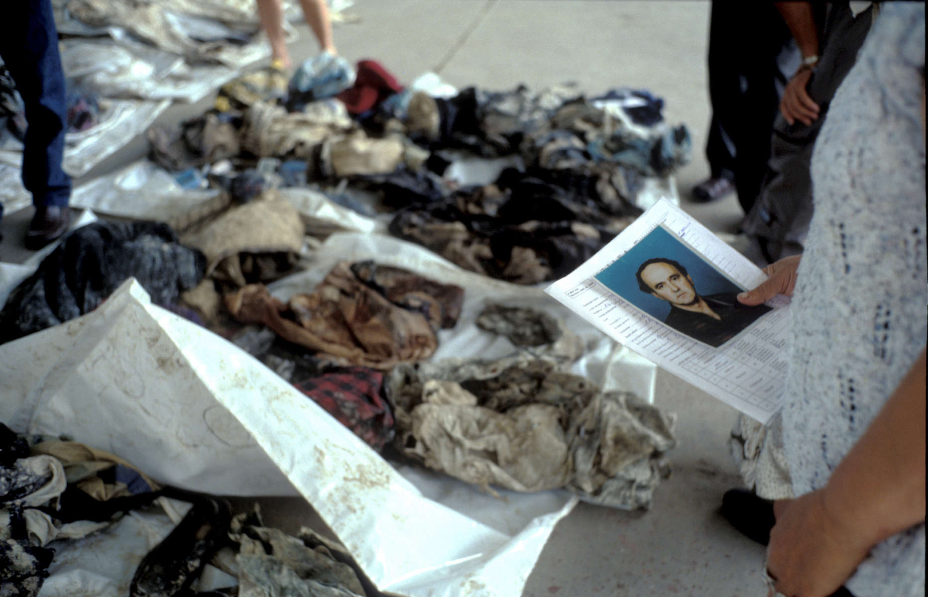 During a public viewing of exhumed remains, a woman holds a photograph of her brother, who disappeared during the 1992 \{quote}ethnic cleansing\{quote} campaign waged by Serbs against their Muslim neighbors. At her feet is a pile of clothes found with bodies exhumed from a mass grave.