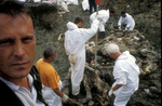 Asim Hadzic, left, a police crime technician, stands at the rim of a mass grave of Srebrenica victims, as forensic anthropologists work to free remains of bodies from the compacted soil. This grave, one of twelve found along a rural road, is a \{quote}secondary\{quote} grave -- meaning that the bodies were originally buried elsewhere, and then dug up, moved and hastily reburied by Serbs who were trying to cover up evidence of the 1995 massacre of some 7,000 to 8,000 Muslim men and boys who were killed when the U.N. \{quote}safe haven\{quote} of Srebrenica was overrun by Serb forces.