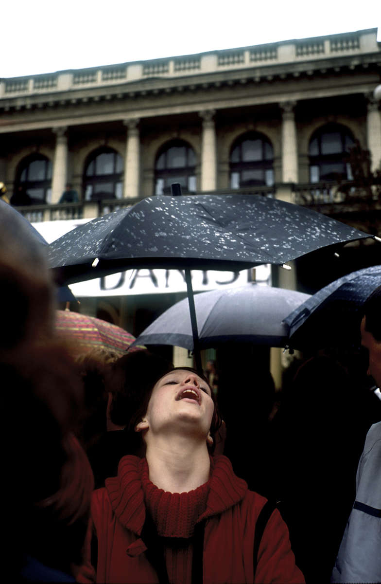 A girl throws back her head in the rain while waiting for film director Danis Tanovic to appear at a rally in his honor. Tanovic, who won an Oscar a few days earlier for his film about the war in Bosnia, \{quote}No Man\'s Land,\{quote} came home to celebrate, arriving the day before the tenth anniversary of the beginning of the siege of Sarajevo.