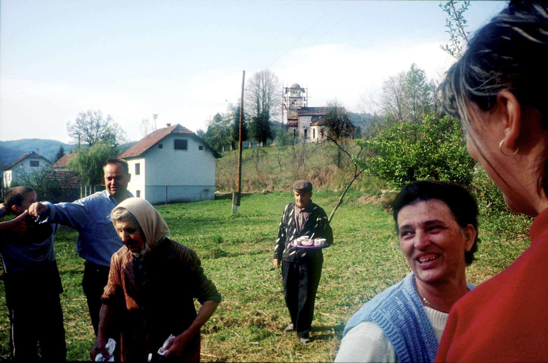 Serb families gather for coffee in the village of Bocinja. Although Serbs lived in the village throughout the war, they fled once the cease fire was signed in the fall of 1994. Several Islamic mujahideen, who had come from Arab countries to fight during the war, moved in to the village and refused to leave when Serb owners wanted to return. International and Bosnian officials finally intervened and removed the mujahideen. As they left, the mujahideen damaged several houses, as well as the Orthodox church in the background, which was being repaired at the time the photo was taken.