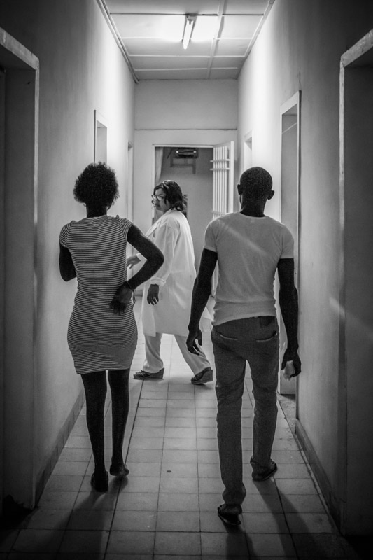 After discussing various family planning methods with a counselor, this young couple decide to get a contracpetive implant that will last for 5 years. They are in their early twenties and already have four children. They follow the doctor to a room to get the procedure done, at a clinic in Kinshasa. September 2016.
