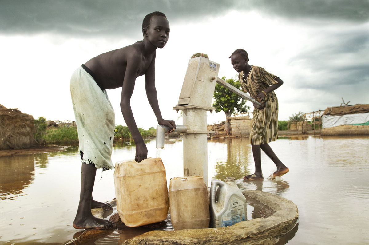 Children fetch water from the hand pump near their flooded homes.  Aweil is in a relatively low-lying location and suffers from seasonal flooding.  The floods have been exacerbated by human factors with insufficient drainage and newly constructed roads interrupting natural drainage patterns.Aweil, Northern Bahr el Ghazal State