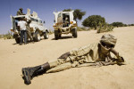 A rebel from the Sudan Liberation Army lounges in front of two  United Nations African Union Mission in Darfur (UNAMID) armoured personnel carriers during a meeting between SLA commanders and peace envoys from the UN and African Union.Umm Rai, Northern Darfur State