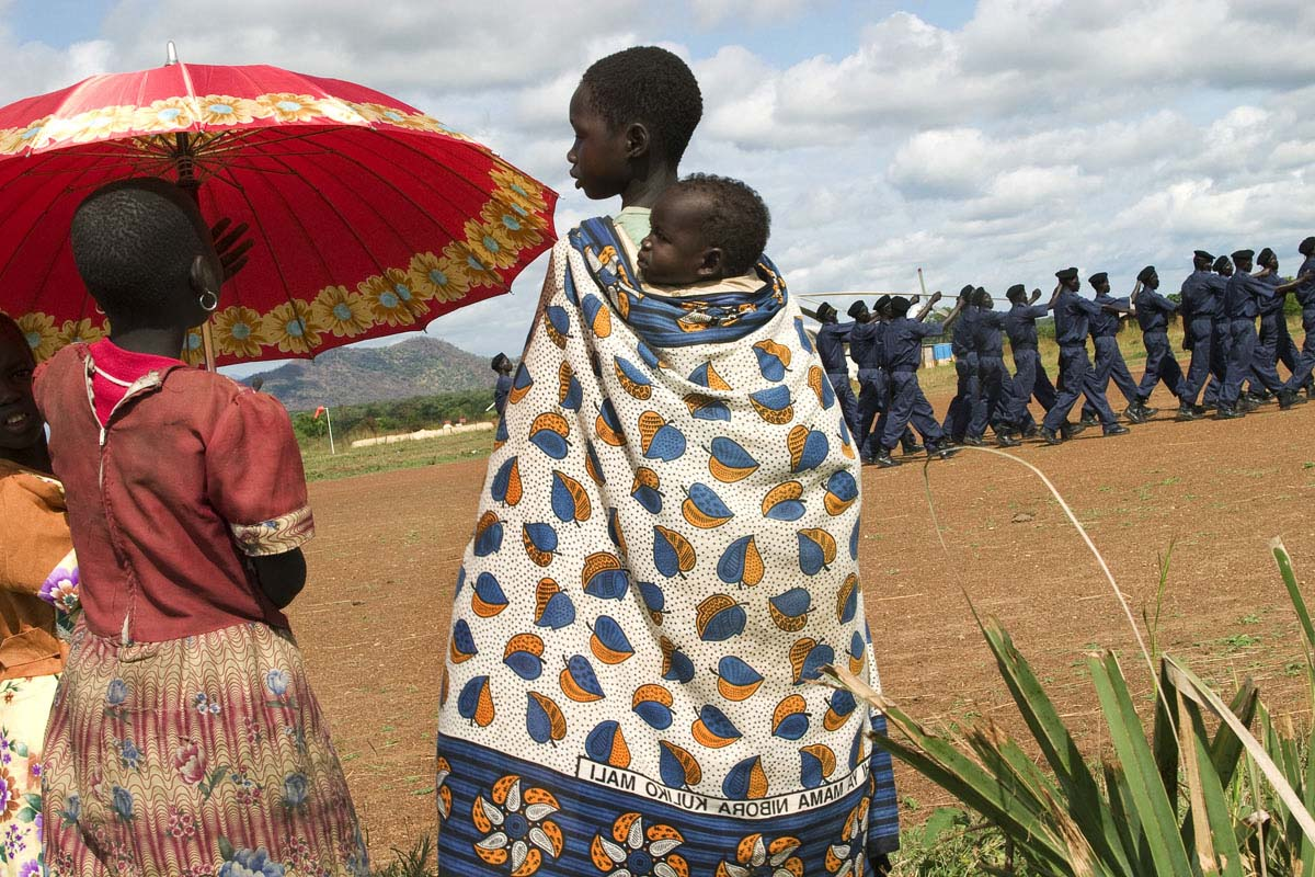 Young girls watch as newly trained Southern Sudan Police Service cadets parade on the airstrip.  Many SPLA soldiers were transferred to other uniformed services including the police, prisons and wildlife following the signing of the CPA.Torit, Eastern Equatoria State