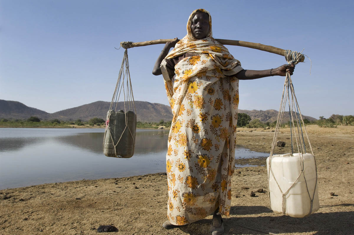 A woman collects water from a lake.  Bau is located in central Blue Nile State and formed a part of the long frontline during the north-south civil war and witnessed intense fighting.Bau, Blue Nile State