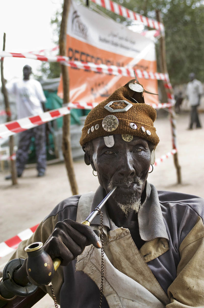 A Dinka elder smokes his pipe outside of a registration center for the referendum.  Eligible voters were registered in all regions of Sudan along with eight foreign countries with a large southern Sudanese Diaspora presence.Pachong, southern Sudan