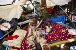 A southern Sudanese returnee sits in her makeshift shelter in the football stadium after arriving from northern Sudan.  She waited for months for onward transportation to her home village.Malakal, southern Sudan