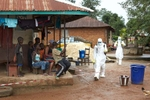 A decontamination team moves between houses in Tonkolili, Sierra Leone