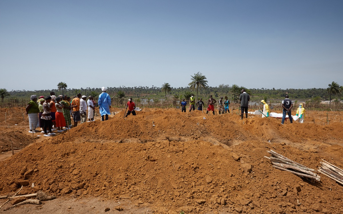 Families and workers are kept at a safe distance as an Ebola victim is buried in a safe and dignified manner. Waterloo, Sierra Leone