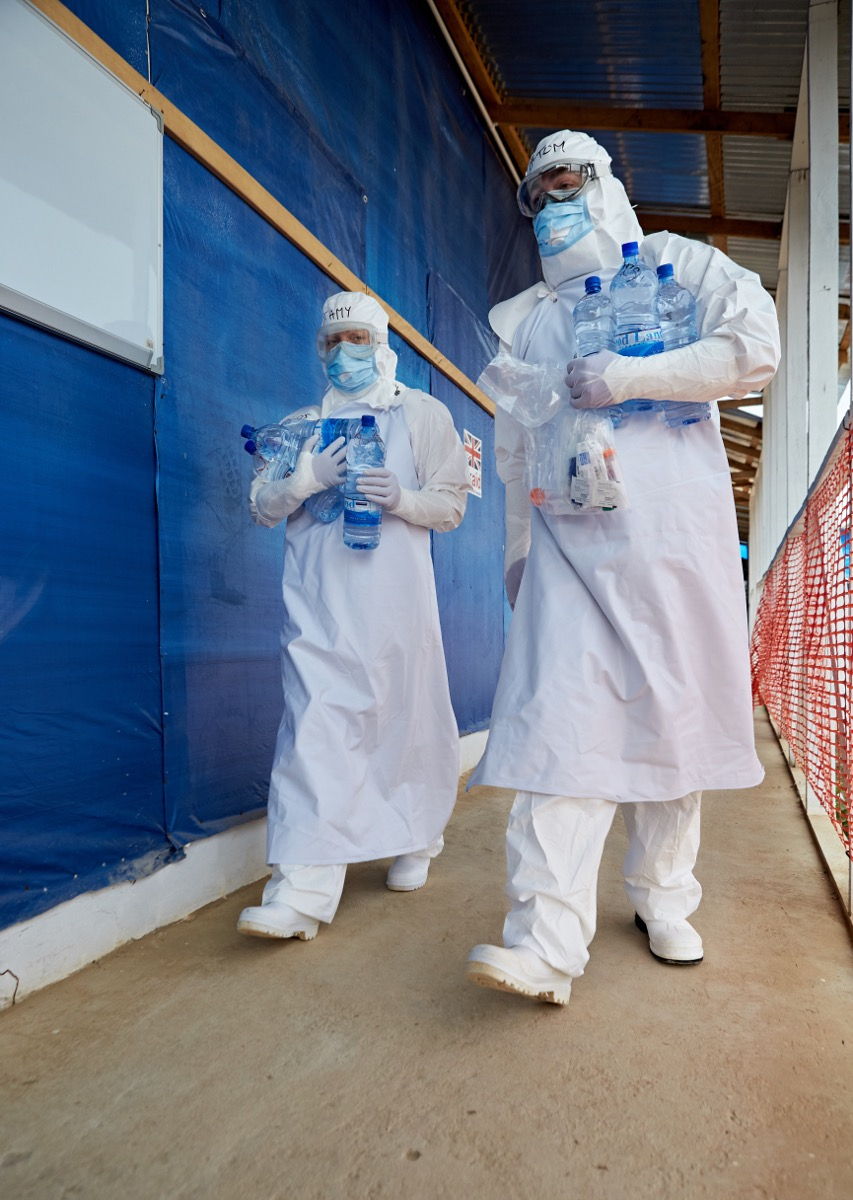 UK NHS staff wearing full PPE entering the red zone at Kerrytown Ebola treatment centre. Sierra Leone