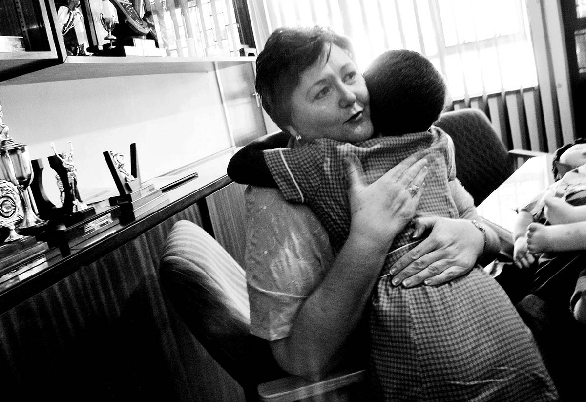 Tinka Labuschagne, a senior education specialist with the South African Ministry of Education comforts a 10yr old student. The previous day the girl disclosed to her teacher that her brother and two of his friends had been sexually abusing her since she was 6. She alleged that she had been raped, sodomised and forced to perform oral sex. She had severe problems with her eyes, a sore throat, vaginal discomfort, and was suspected to be suffering from gonorrhoea. PLACE: ThembisaDATE: January 2006