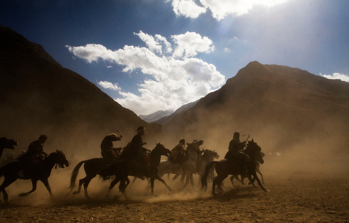 Khenj, Afghanistan: The men of Khenj, Afghanistan, compete in a game of Buzkashi. The popular game, banned under that Taliban, is a match between villagers on horseback pitted against each other to grab the carcass of a dead goat, or in this case, a dead calf, with its head cut off, from one location in the playing field, around a flag and set in a circle in another location. Each time a rider successfully completes the task he is cheered by the crowed gathered under the leaves of Fall  in the shadow of the Hindu Kush.