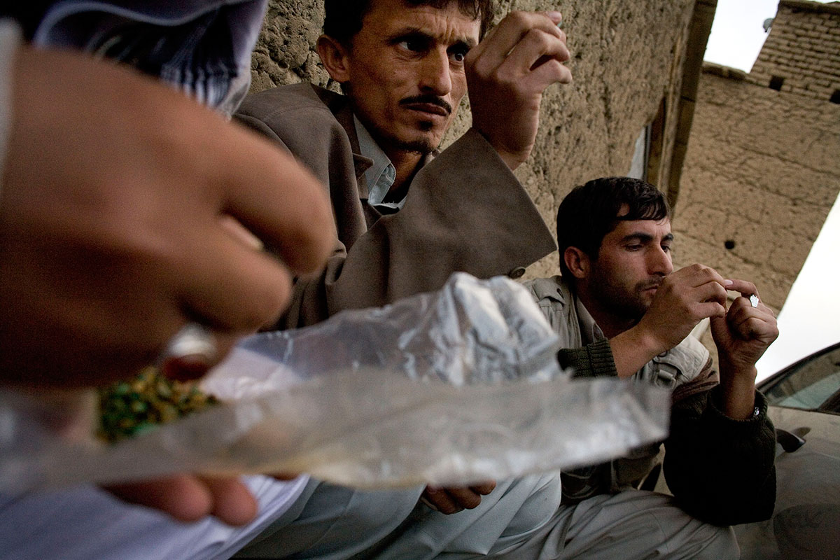 October 26, 2007- Khenj, Afghanistan: Emerald buyers from Kabul, Hiatullah, left, and Gulalam, right, look at a pocket full of emeralds brought down the mountain in the village of Khenj, Afghanistan on Friday, October 26, 2007. Most miners keep their emeralds in a plastic package. Usually the partners in a mine will weigh, count, then wrap the emeralds they find, signing the wrapping to insure they all agree on what was found. Then the package is opened again when it reaches the village and is sold.