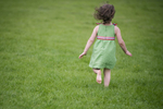 girl running through the grass during Hoboken family portrait session