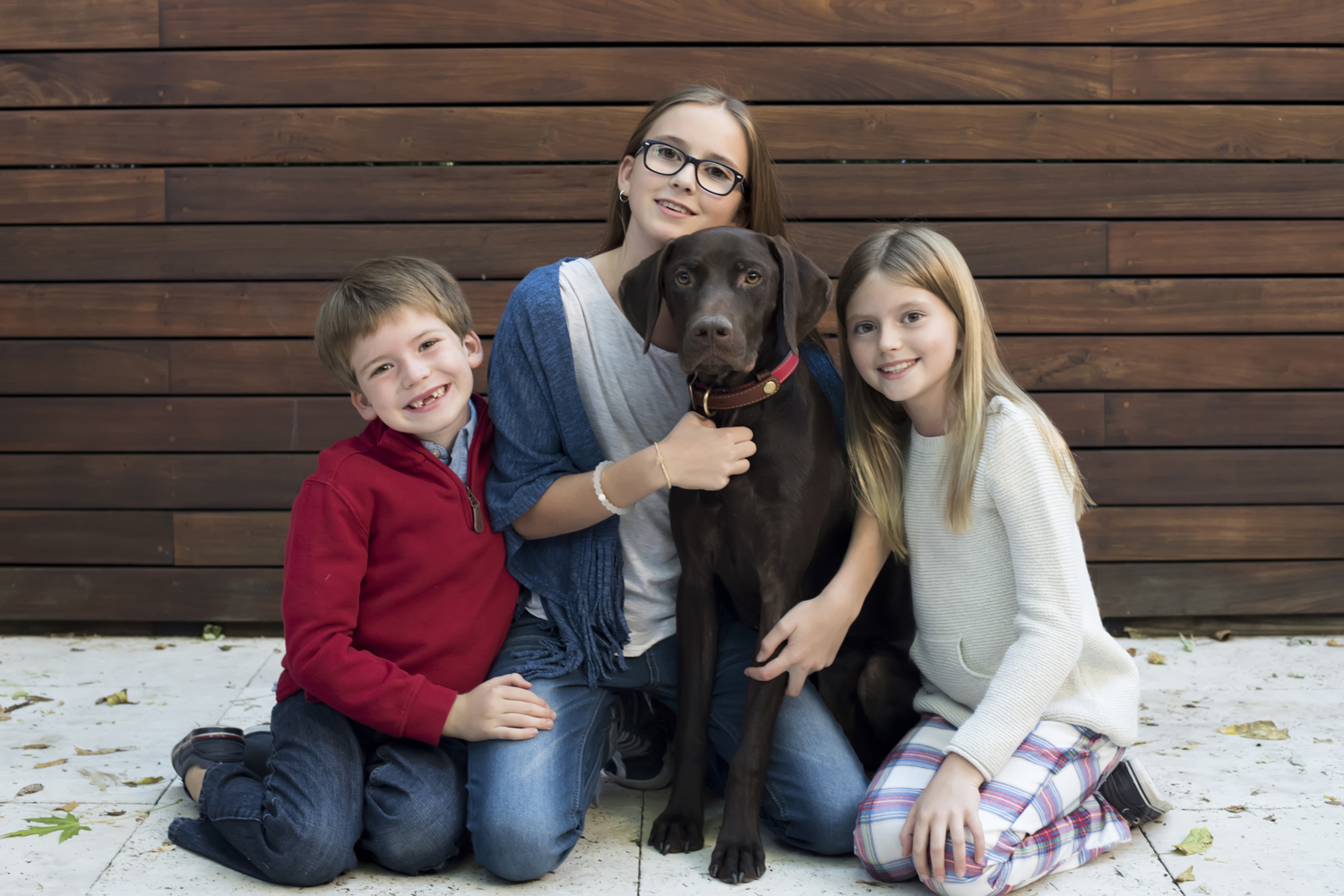 three kids and their dog in their Hoboken backyard for family portraits