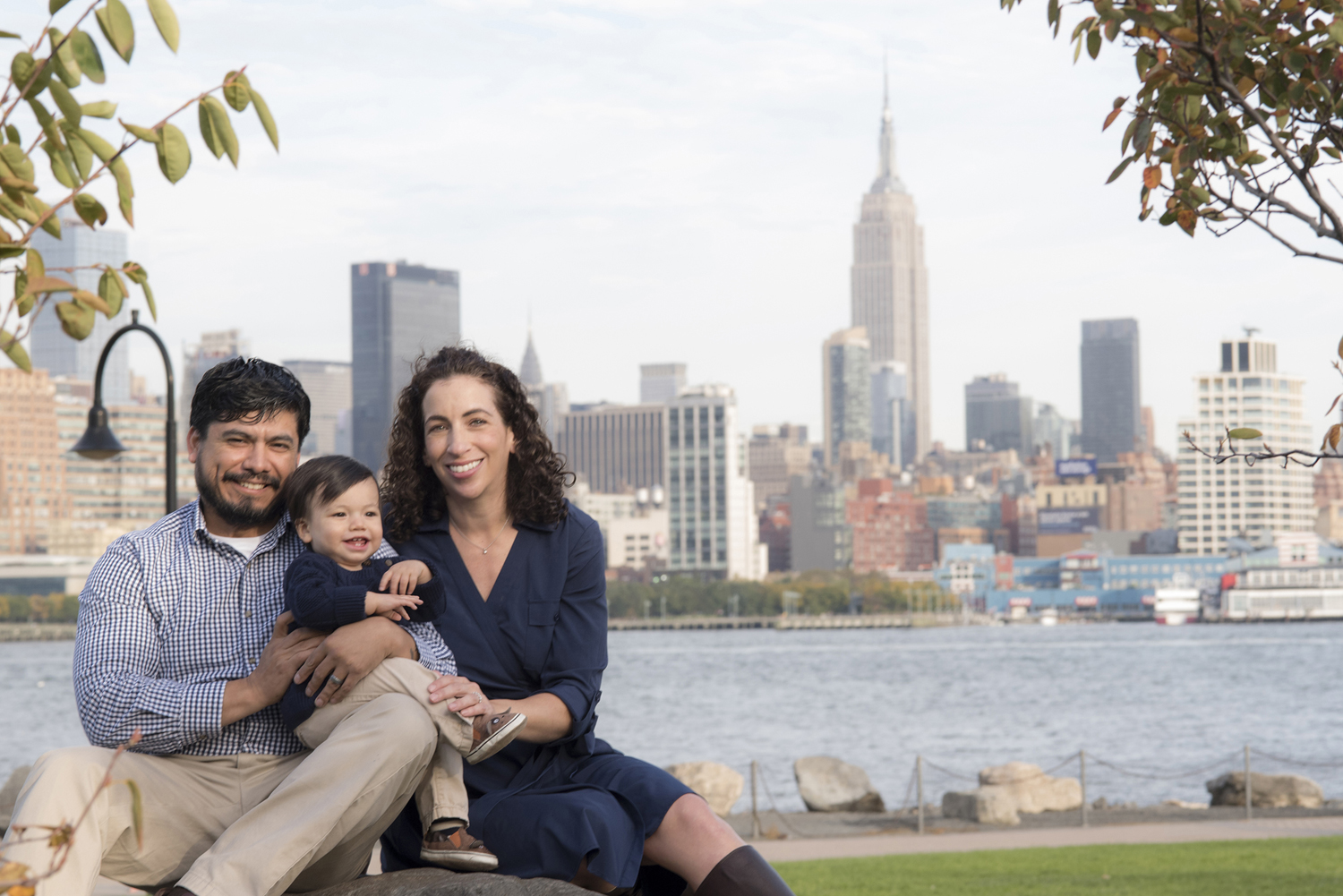 Family of three in Hoboken against the NYC skyline for their family photos