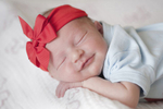 newborn girl sleeps during her newborn photography portrait session