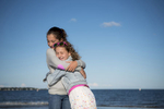 sisters embrace on beach at Tod's Point in Greenwich, CT