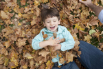 boy falls into a leaf pile during family photo session in Jersey City