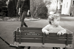 boy rides in his wagon during family portrait session