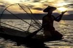 Fisherman Kneeling in Boat at Sunset