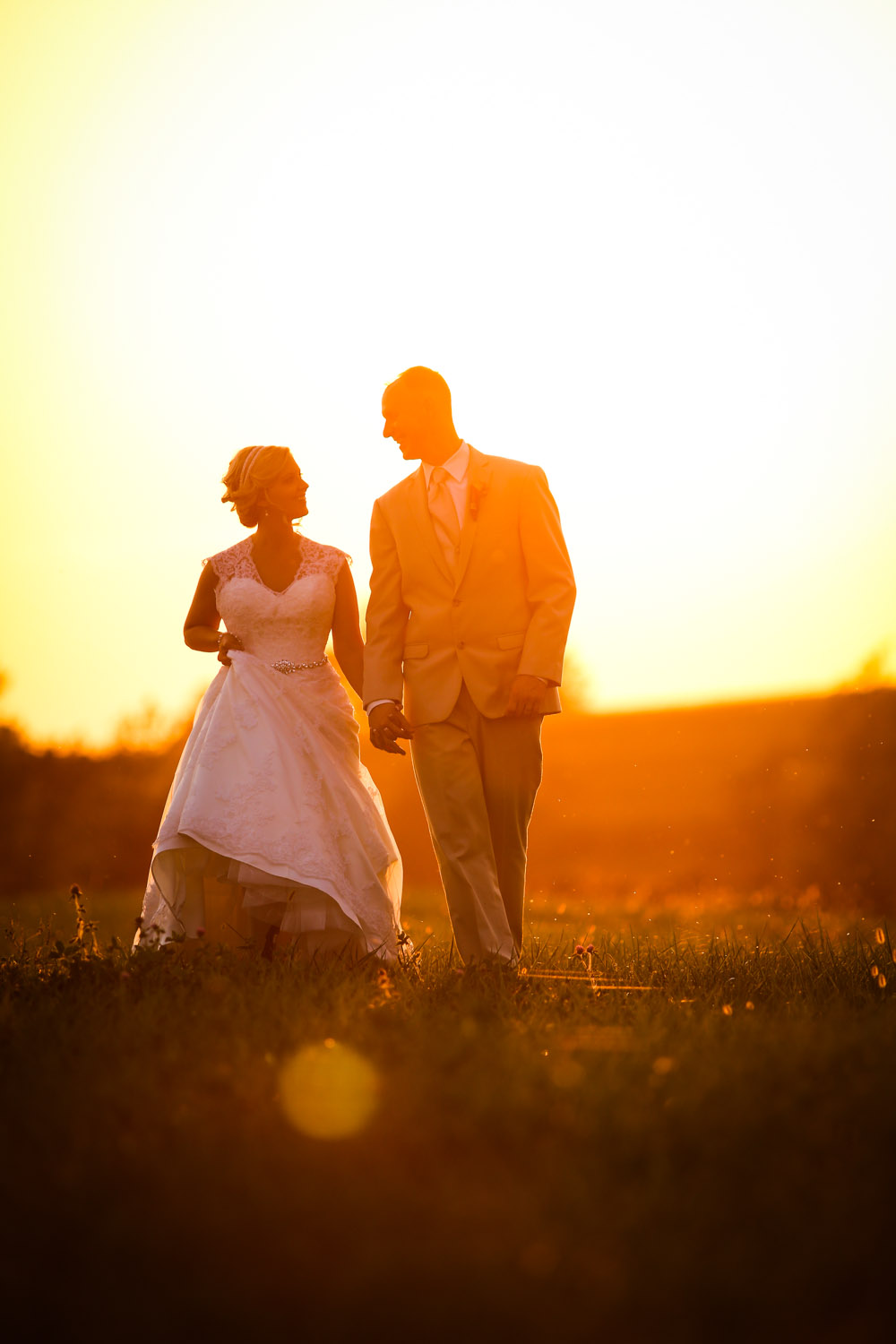 A bride and groom walk in the sunset.